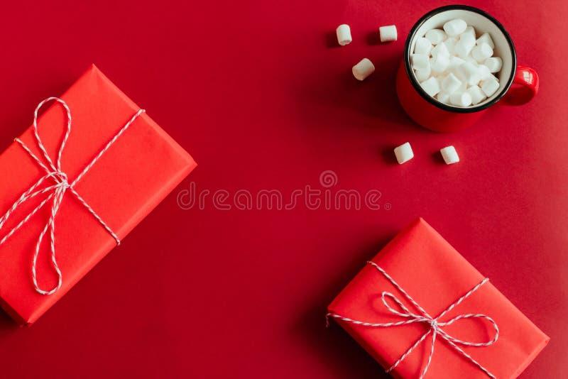 boîte-cadeau et tasse rouges avec le cadre de guimauves sur le fond rouge photos stock