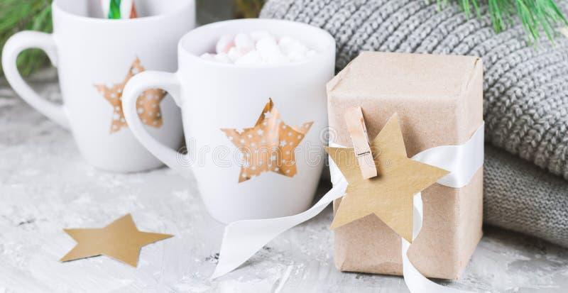 boîte-cadeau et tasses avec des guimauves et des cannes de sucrerie sous l'arbre de Noël image stock