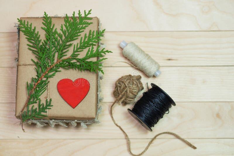 Boîte-cadeau fait de papier d'emballage, attaché avec la dentelle Un coeur rouge en bois photographie stock libre de droits
