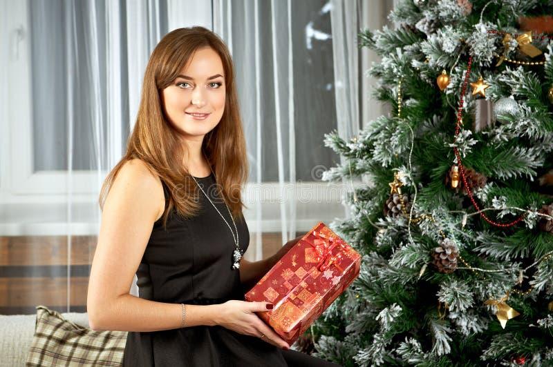 Boîte-cadeau heureux de prise de sourire de jeune femme dans des mains photographie stock