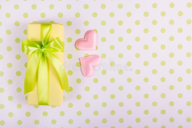 Boîte-cadeau jaune avec le ruban de satin et deux coeurs roses sur un fond de point de polka photos stock