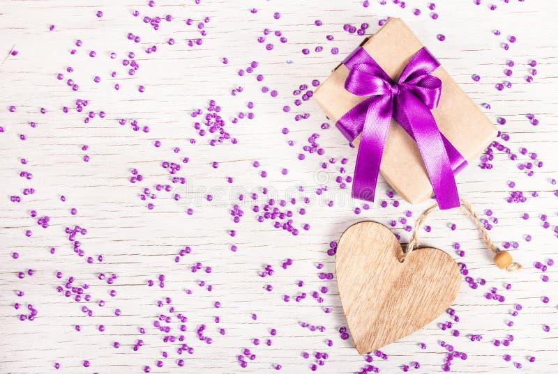 Boîte-cadeau lumineux avec l'arc de satin et coeur en bois sur un fond blanc avec des fausses pierres Jour du ` s de St Valentine images libres de droits