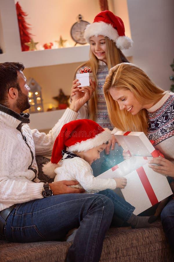 Boîte-cadeau magique ouvert de Noël de garçon avec la famille image stock