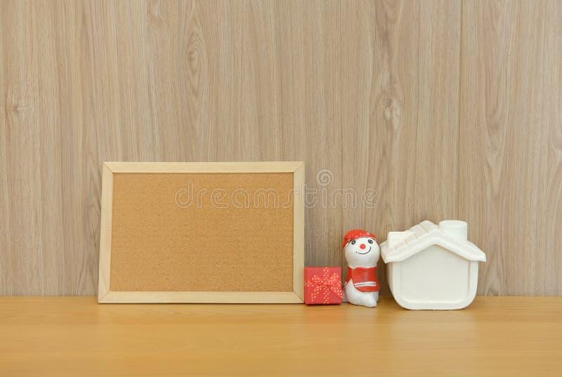boîte-cadeau miniature de maison de bonhomme de neige de panneau de liège sur la table en bois de bureau photo libre de droits
