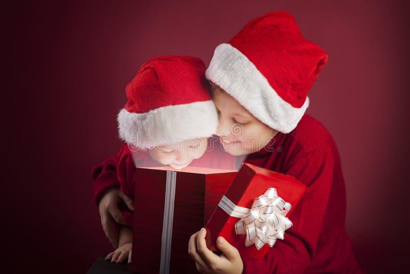 Boîte-cadeau ouvert de Noël de deux garçons photo stock