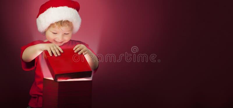 Boîte-cadeau ouvert de Noël de garçon heureux image stock