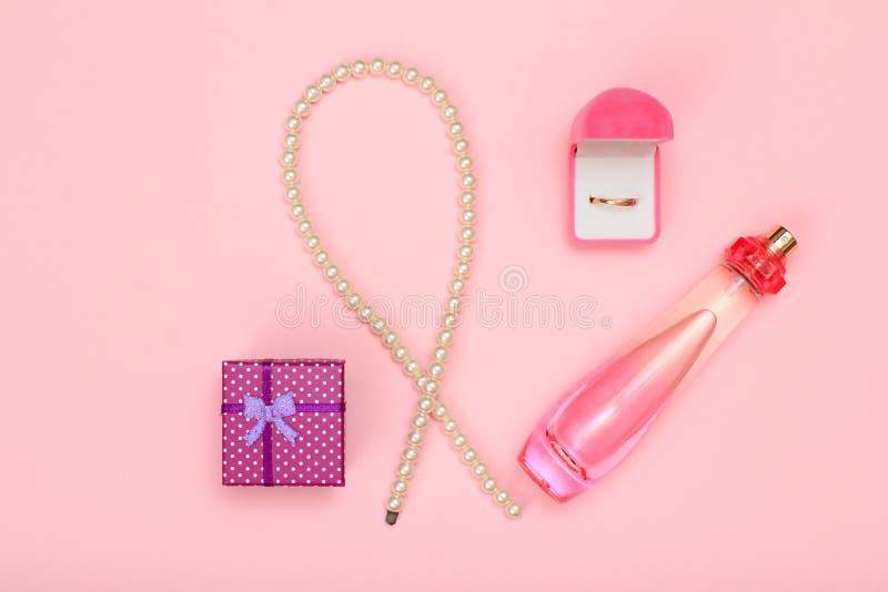 Boîte-cadeau, perles, bouteille de parfum et anneau d'or dans la boîte sur un fond rose Cosmétiques et accessoires de femmes photo libre de droits