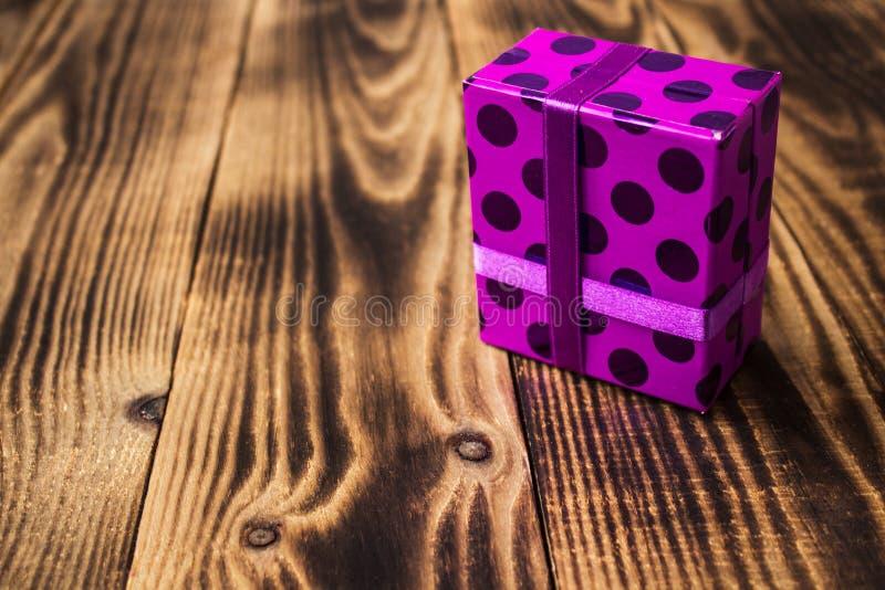 Boîte-cadeau pourpre actuel sur le fond en bois photos libres de droits