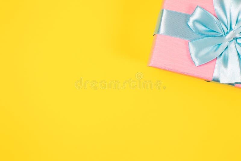 Boîte-cadeau rose attaché avec le ruban bleu avec l'arc au dessus sur le fond jaune Copiez l'espace pour le texte Configuration m photo stock