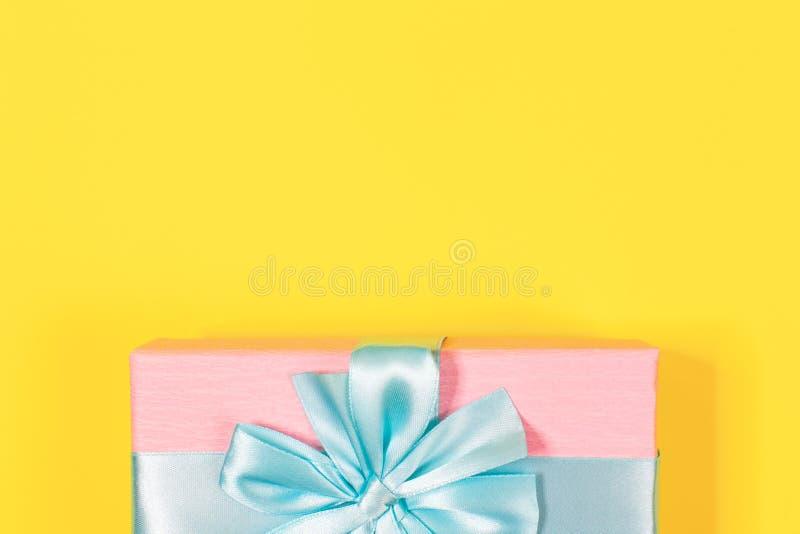 Boîte-cadeau rose attaché avec le ruban bleu avec l'arc au dessus sur le fond jaune Copiez l'espace pour le texte Configuration m photographie stock libre de droits