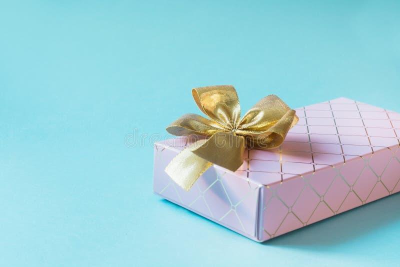 Boîte-cadeau rose femelle avec le ruban d'or sur le rose en pastel ivre Anniversaire Copiez l'espace image libre de droits