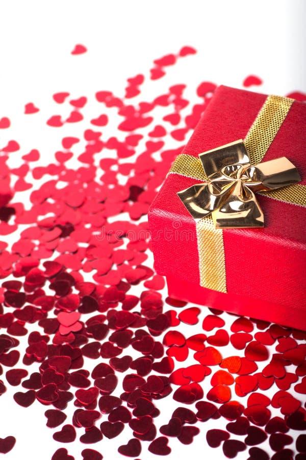 Boîte-cadeau rouge avec l'arc d'or et beaucoup de petits coeurs rouges sur le blanc photographie stock libre de droits