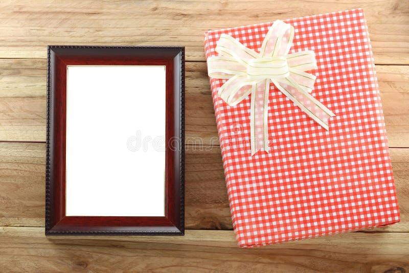 Boîte-cadeau rouge avec le cadre de tableau en bois vide sur le fond en bois images libres de droits
