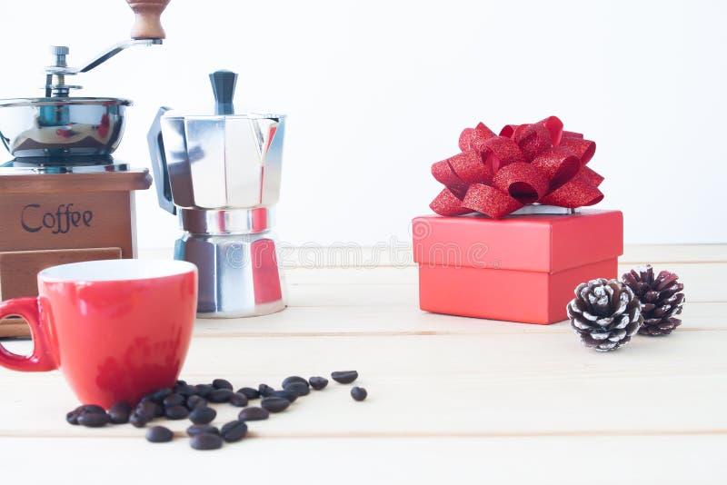 Boîte-cadeau rouge avec le pot de café, la broyeur de café, la tasse rouge et les grains de café rôtis sur la table, foyer sélect photo stock