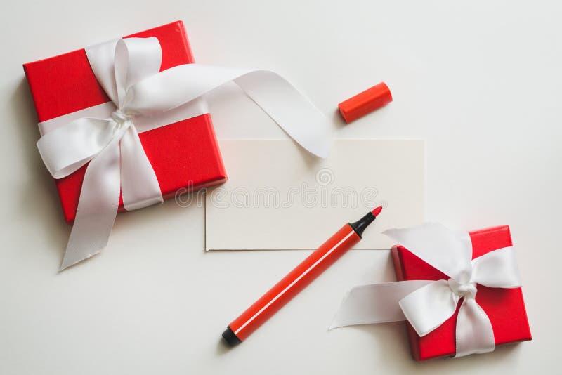 Boîte-cadeau rouges attachés avec un ruban blanc, un marqueur et la carte avec l'espace de copie sur un fond clair photo stock