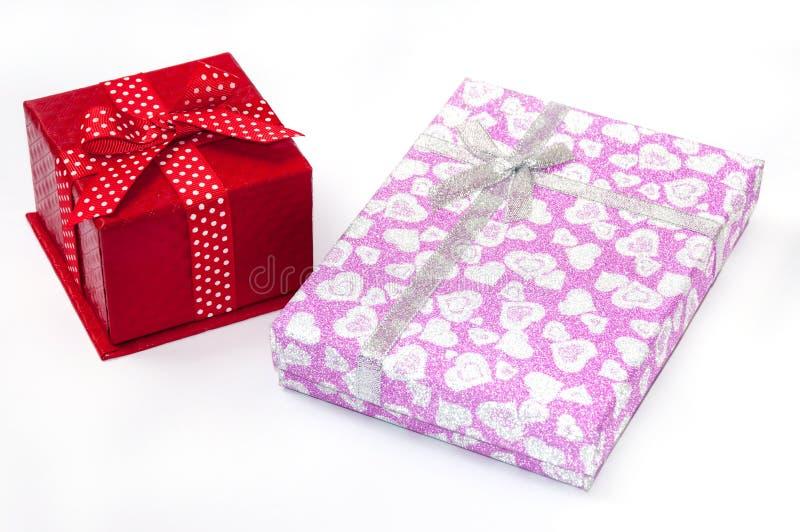 Boîte-cadeau rouges et roses avec des arcs images stock