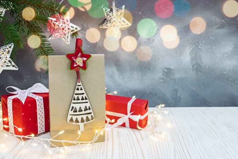 Boîte-cadeau rouges, sac de papier de cadeau, branche d'arbre verte de sapin sur le christm photographie stock libre de droits