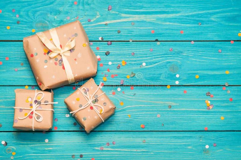 Boîte-cadeau sur le fond en bois de turquoise avec des confettis photos libres de droits