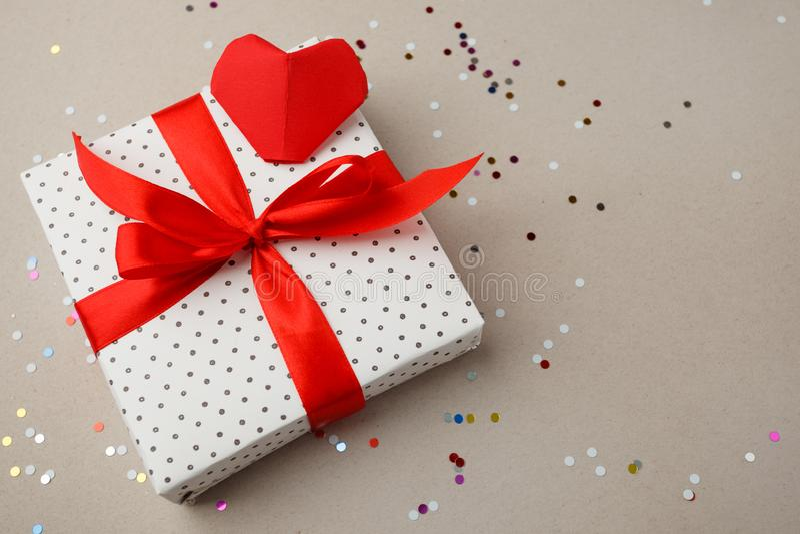 Boîte-cadeau sur le fond gris avec le coeur et les confettis Étonnez votre aimé Le concept du jour de St Valentine, mariages images libres de droits