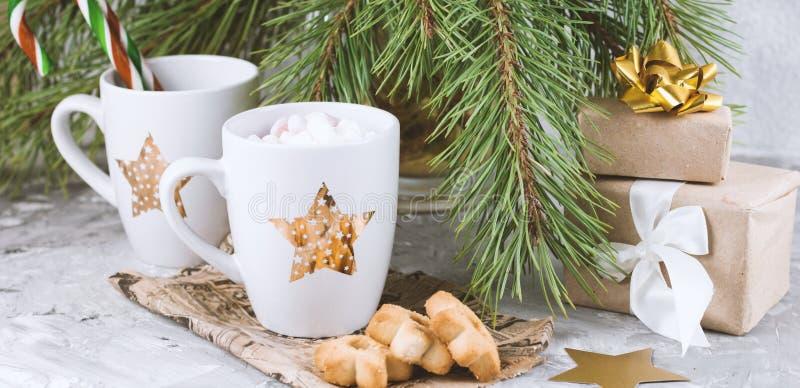boîte-cadeau, tasse avec la boisson décorée de la guimauve et biscuits de forme d'étoile près du béton à feuilles persistantes de photo libre de droits