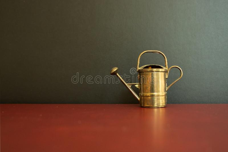 Boîte d'arrosage miniature de cru d'or devant le fond noir photos libres de droits