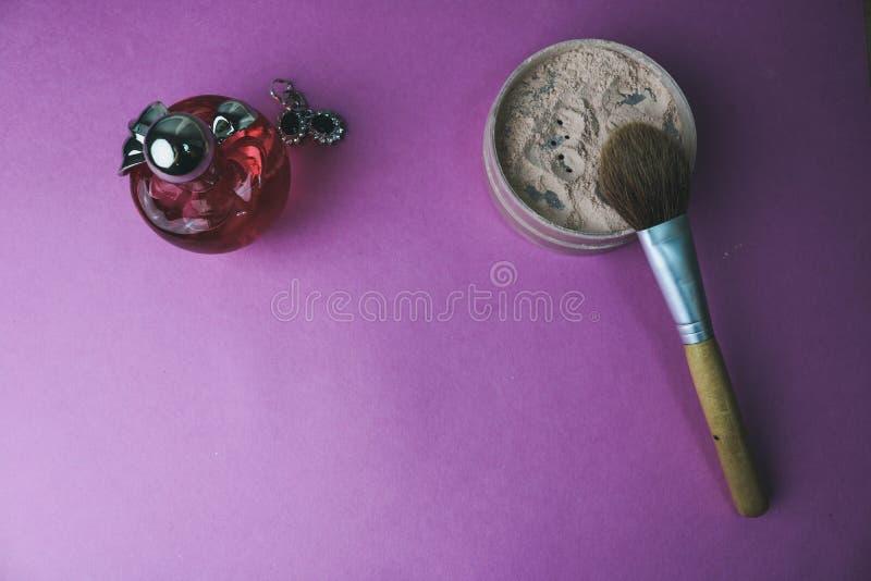Boîte de beauté, poudre avec une brosse brune de petit somme pour le maquillage, parfum rose et boucles d'oreille sur un fond Con photographie stock libre de droits