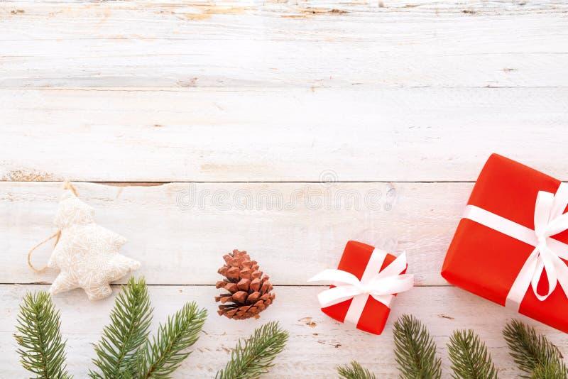 Boîte de cadeaux de cadeau de Noël et éléments rouges de décoration sur le fond en bois blanc photos libres de droits