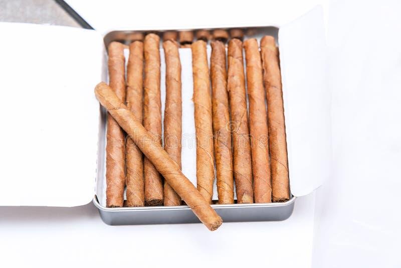 Boîte de cigarillos sur un fond blanc Sur la boîte est un cigarillo images stock
