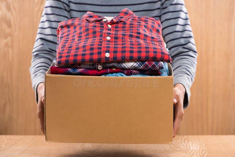 Boîte de donation pour des pauvres avec l'habillement dans des mains masculines photos libres de droits