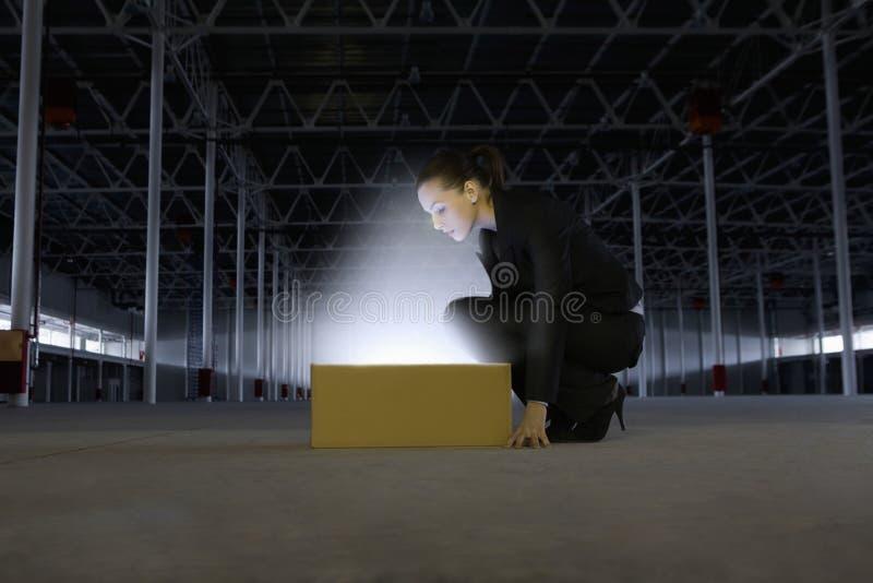 Boîte de Looking At Glowing de femme d'affaires dans l'entrepôt vide photo stock