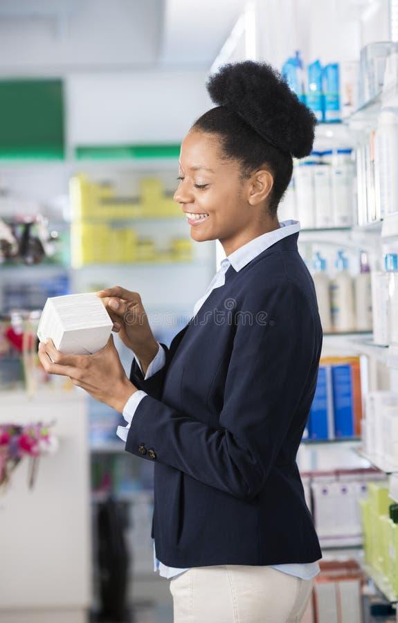 Boîte de médecine de Reading Instructions On de femme d'affaires dans la pharmacie photos stock