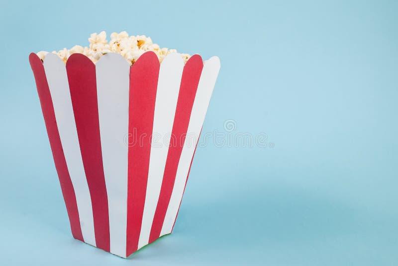 Boîte de maïs éclaté sur le fond bleu et d'espace pour le texte photos stock
