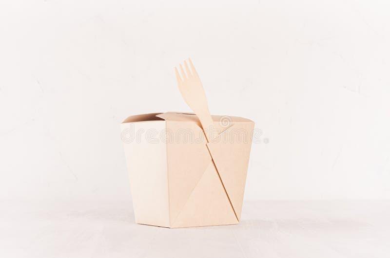 Boîte de papier brune à nouilles de blanc et fourchette en bois pour le traiteur de nourriture sur le fond blanc clair mou, maque photo stock