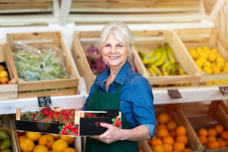 Boîte de participation d'employé de magasin avec les fraises fraîches dans le magasin organique de produit images libres de droits