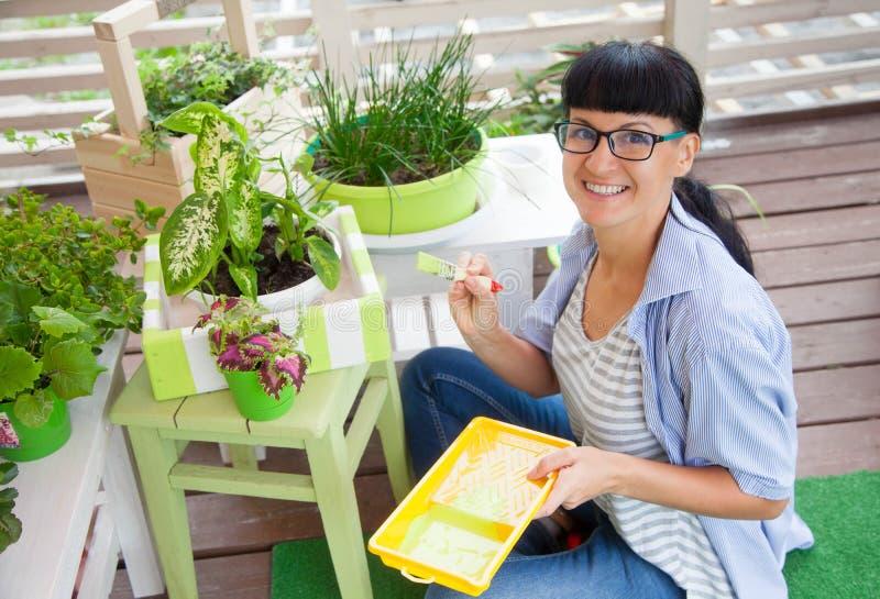 Boîte de sourire heureuse de peinture de femme pour des fleurs Bacs de fleur verts image libre de droits