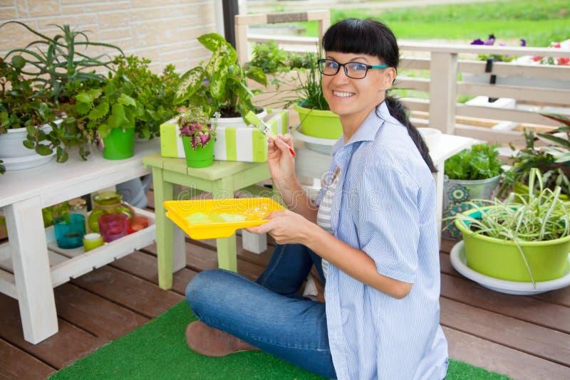 Boîte de sourire heureuse de peinture de femme pour des fleurs Bacs de fleur verts photographie stock