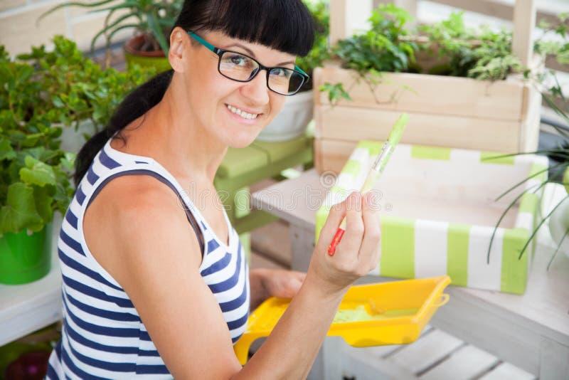 Boîte de sourire heureuse de peinture de femme pour des fleurs Bacs de fleur verts photographie stock libre de droits