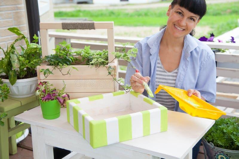 Boîte de sourire heureuse de peinture de femme pour des fleurs Bacs de fleur verts images libres de droits