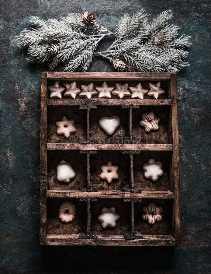 Boîte en bois avec de petites cellules décorées des branches et des cônes de sapin et remplies de biscuits et de pain d'épice de  photographie stock