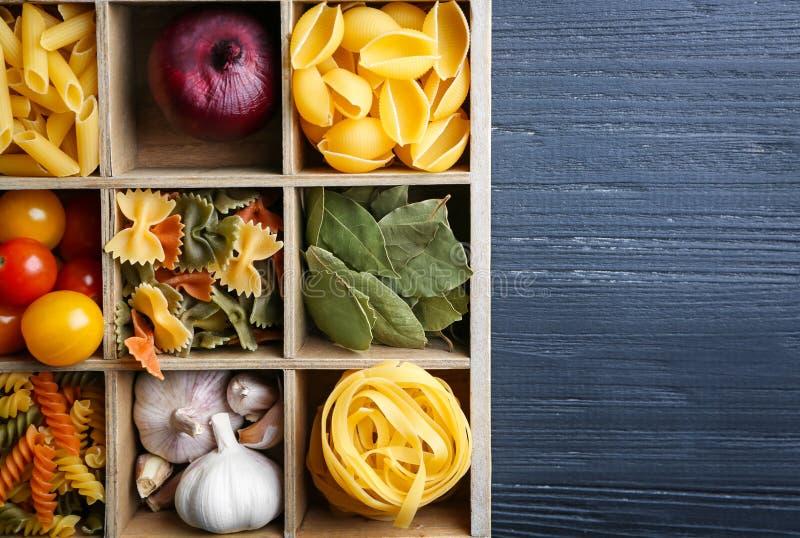 Boîte en bois avec différents pâtes et légumes crus sur la table image stock
