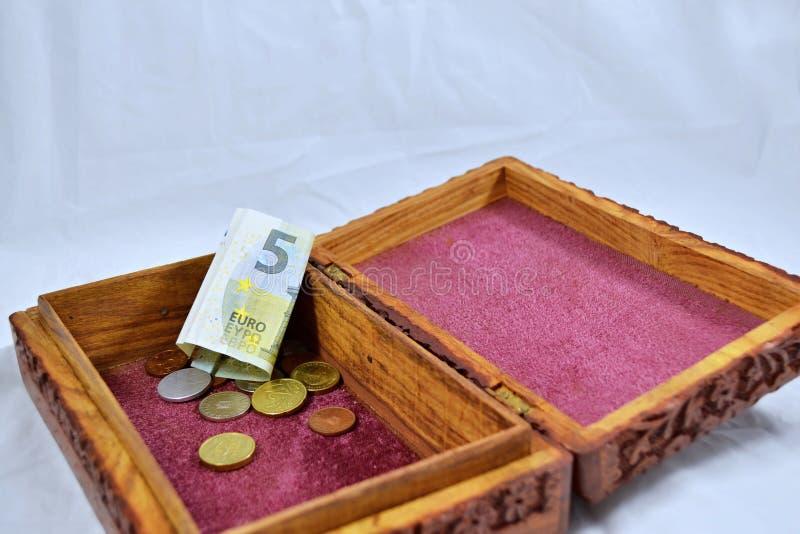 Boîte en bois avec le tapis rouge, les pièces de monnaie et l'euro billet de banque photos libres de droits