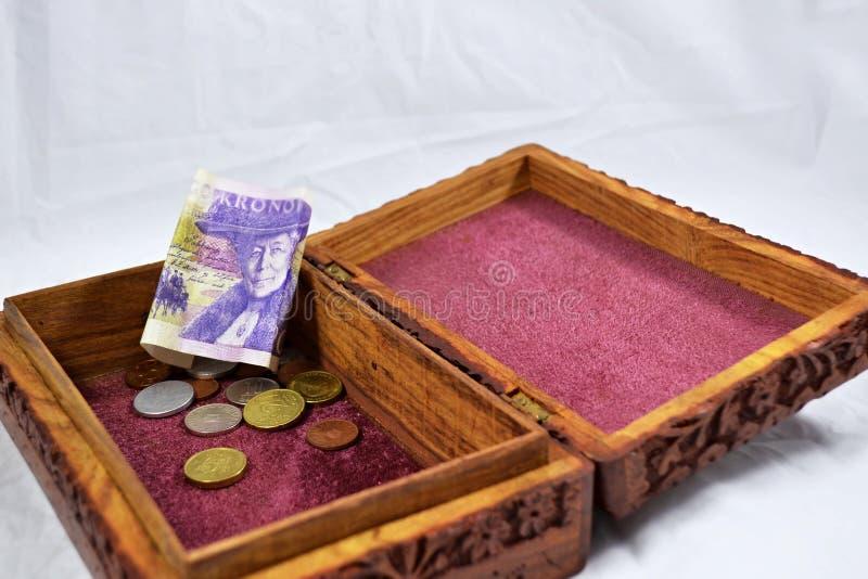 Boîte en bois avec le tapis rouge, les pièces de monnaie et le billet de banque de couronne suédoise photos libres de droits