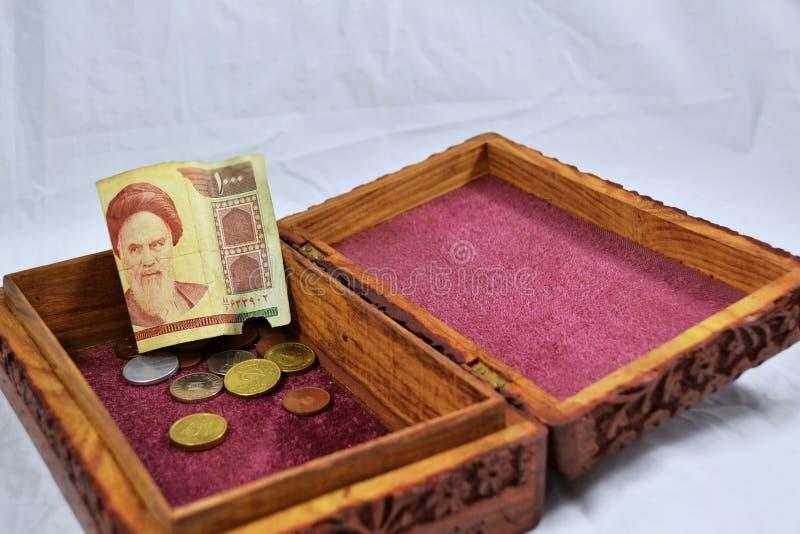 Boîte en bois avec le tapis rouge, les pièces de monnaie et le billet de banque de rial de l'Iran images libres de droits