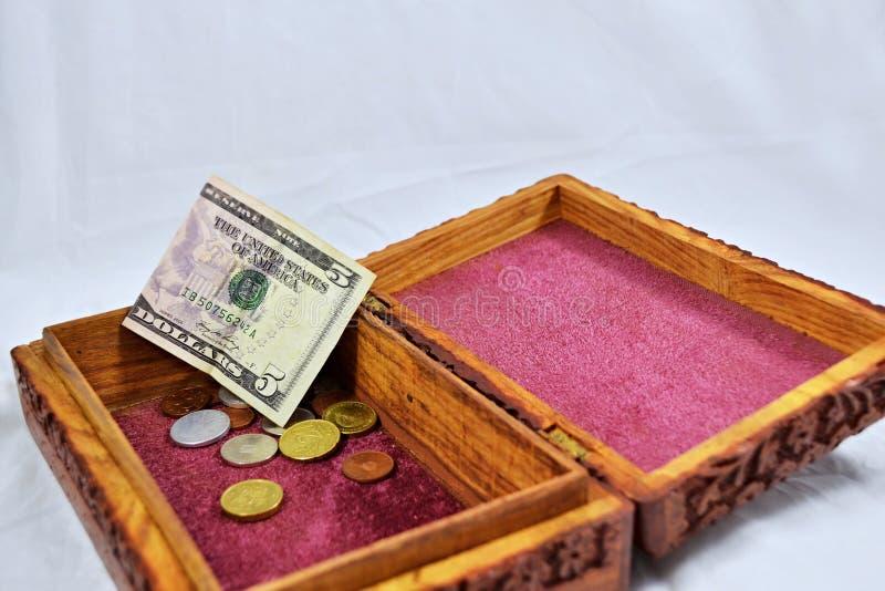 Boîte en bois avec le tapis rouge, les pièces de monnaie et le billet de banque du dollar US image stock