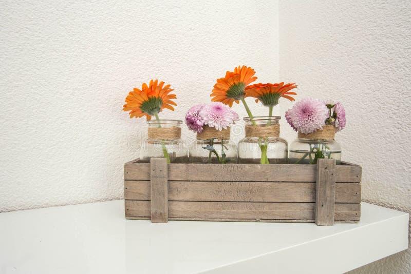 Boîte en bois avec les fleurs oranges et roses sur l'étagère blanche, fond blanc, conception moderne image stock