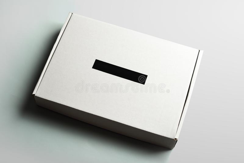 Boîte en carton blanche avec le label noir sur le fond gris de studio image stock