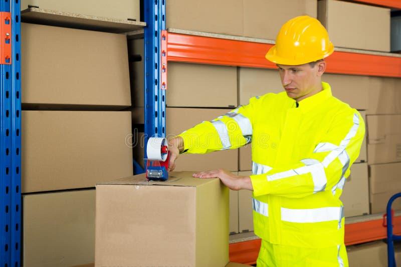 Boîte en carton de cachetage de travailleur avec le ruban adhésif photo stock