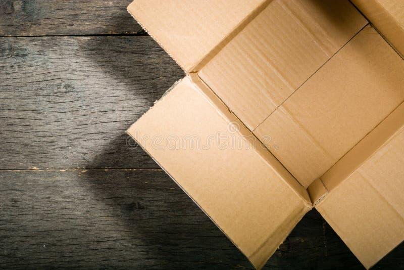 Boîte en carton de place ouverte sur le fond de la vieille table en bois photo stock