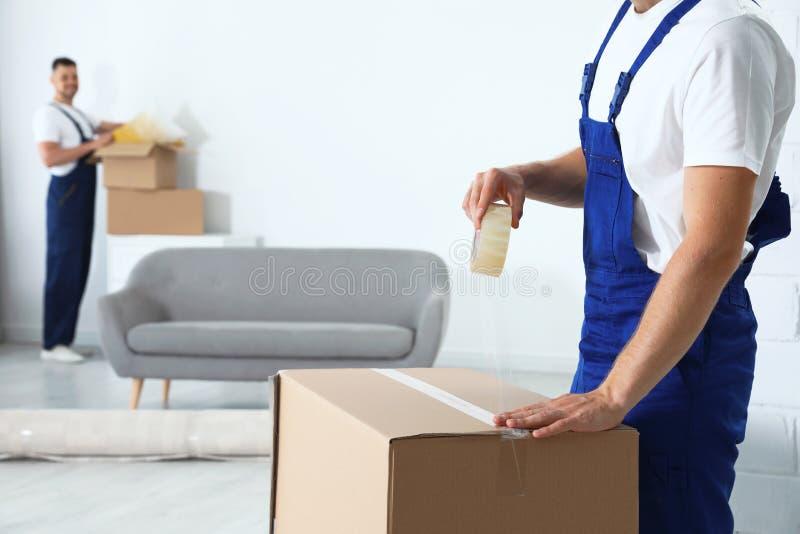 Boîte en carton de scellage en mouvement des employés de service photo stock