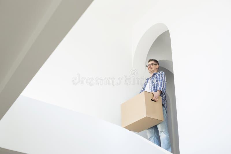 Boîte en carton de transport d'homme dans la nouvelle maison photographie stock